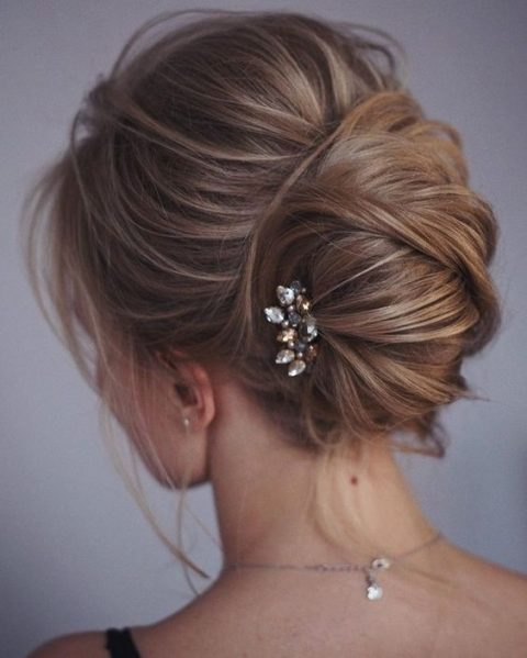 a catchy idea of a messy chignon and twists and locks down and a small rhinestone hairpiece