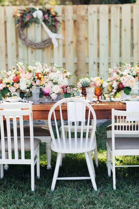 a chic backyard bridal shower setting with lush florals and colorful glasses plus mismatching chairs