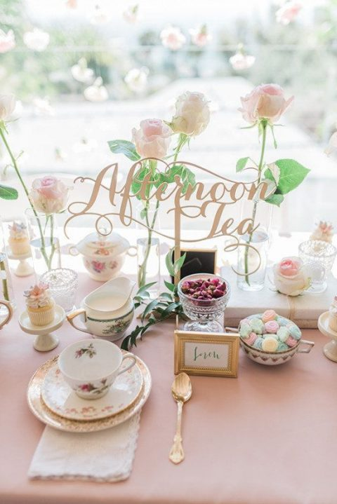 a chic bridal shower setting with blush blooms, a calligraphy topper, tea cups and vintage pieces