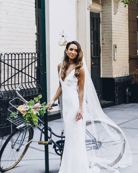a chic minimalist wedding look with a white slip dress and a long veil