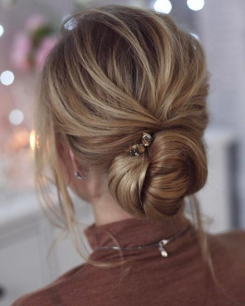 a chic twisted low chignon wedding hairstyle with a bump, locks down and a rhinestone hairpin