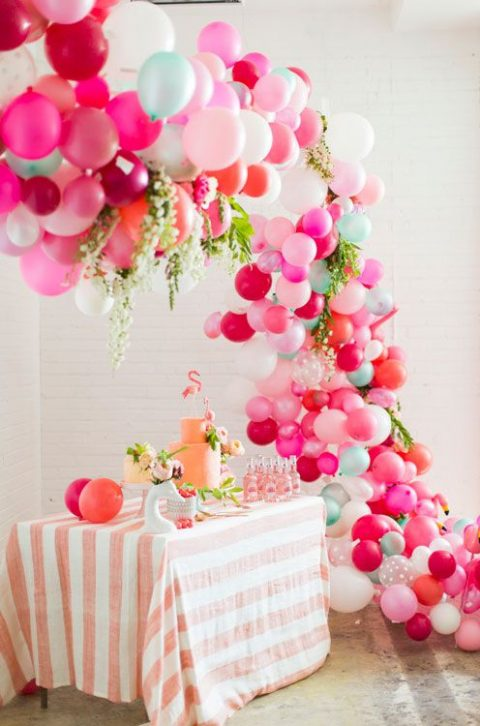 a colorful balloon and tropical leaf arch over a dessert table