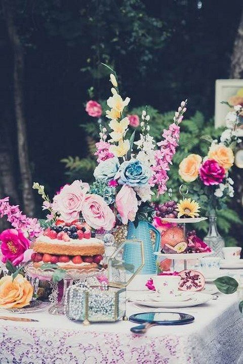 a colorful dessert table with pearls, cakes, fruit, bold bloom arrangements