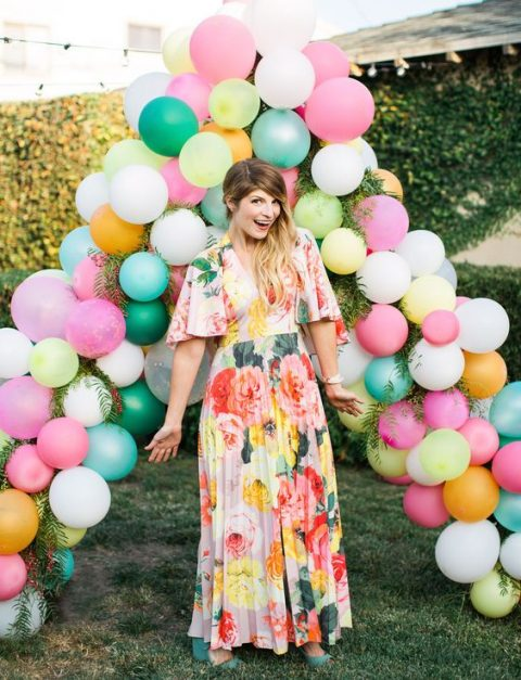a colorful triangle-shaped balloon and greenery wedding arch