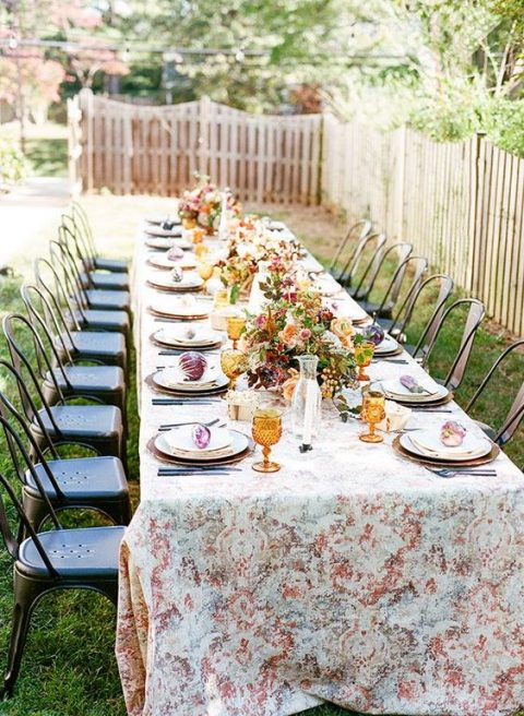 a cool bridal shower table with a printed tablecloth, bright blooms, amber glasses and vintage chairs