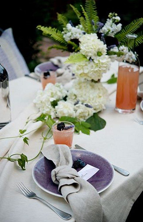 a cool table setting for an outdoor backyard bridal shower, fresh blooms and berries for decor