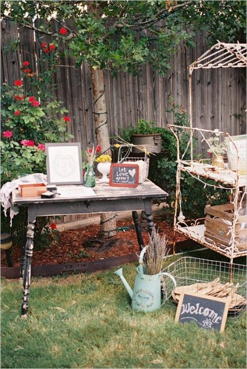 a cozy rustic backyard shower with vintage furniture, a watering can with lavender and welcome signs