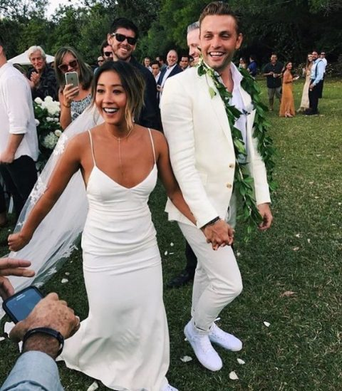 a creamy suit, a white shirt and white sneakers plus a greenery garland for a relaxed tropical groom_s look