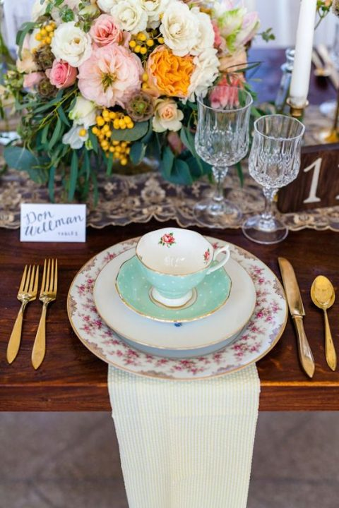 a cute vintage tea party setting with vintage porcelain, gold cutlery and lush blooms