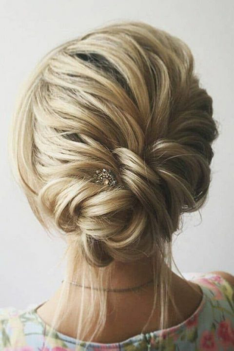 a dimensional low updo with locks down and a rhinestone hairpiece