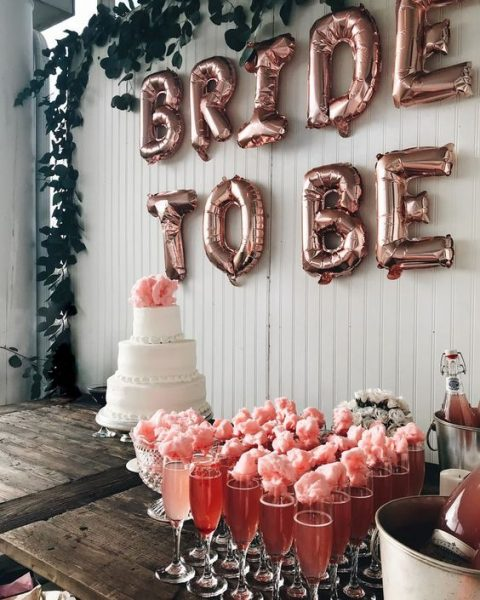 a drink station with pink champagne and cotton candy plus a wedding cake and cool letters in the backdrop
