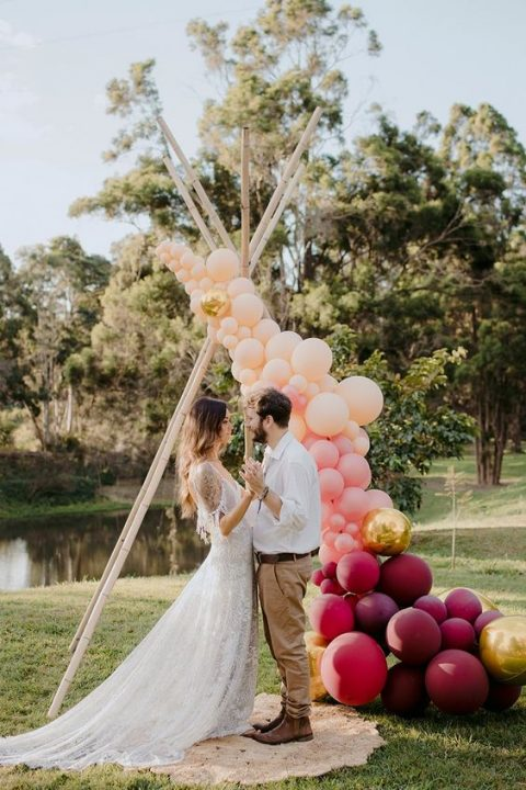 a fresh and modern take on a boho wedding arch with peachy, gold and plum-colored balloons