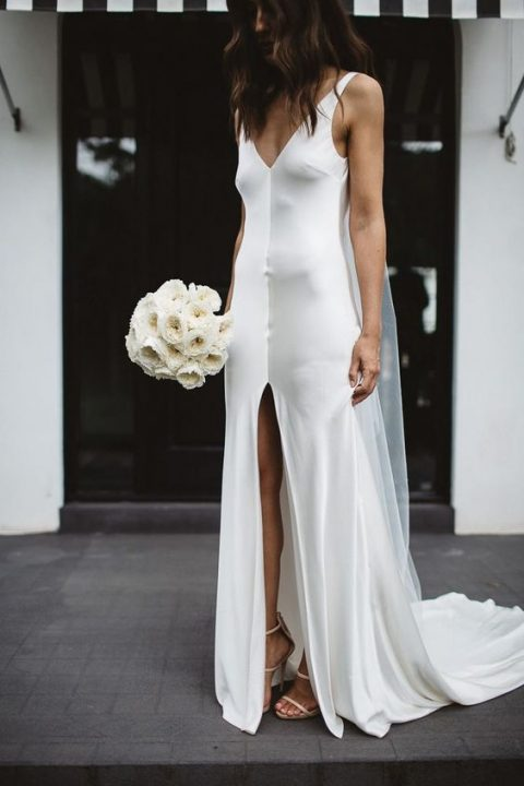 a fresh take on a classic slip dress, a white silk slip gown with a deep V-neckline and a front slit