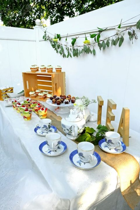 a garden tea party dessert table with a greeneyr garland over it, vintage tea cups and lots of desserts