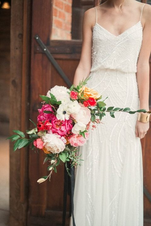 a gorgeous all-sparkling slip wedding dress with a V-neckline and a bright wedding bouquet