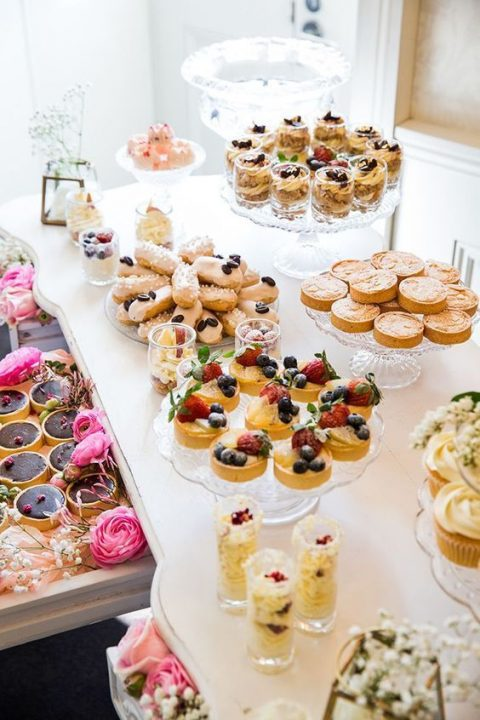 a gorgeous sweets table with delicious cupcakes, cakes, souffles and eclairs