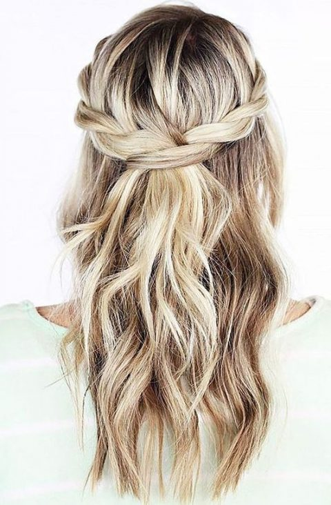 a half updo with a braided halo and waves down