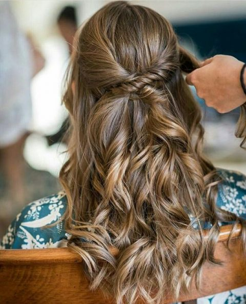a half updo with waves down and a twisted detail