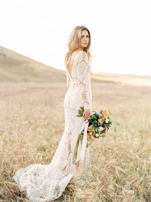 a lace sheath wedding dress with a deep cutout back, long sleeves and a train