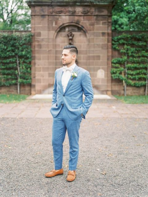 a light blue suit, a white shirt, a white bow tie and amber moccasins