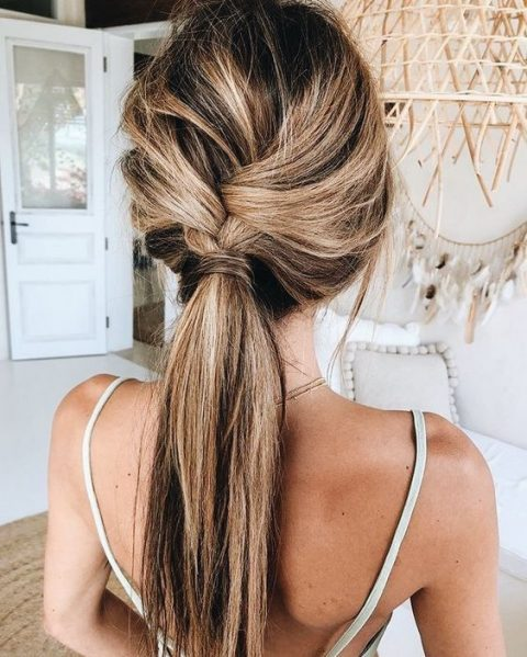 a loose braid into a ponytail is a cool idea for a boho or rustic wedding