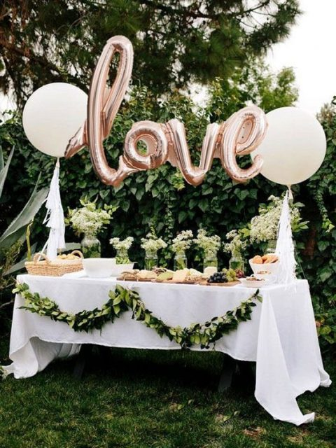 a lovely dessert table with a greenery garland, usual and letter balloos. greenery and neutral blooms
