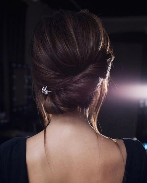 a low asymmetrical twisted chignon with a bump, some locks down and a rhinestone hairpiece for an accent