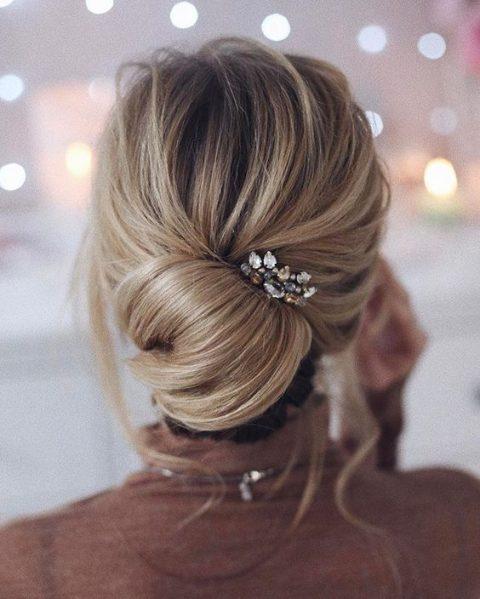 a low chignon hairstyle with a bit of mess, locks down and a rhinestone hairpiece