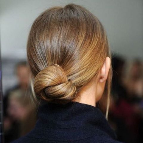 a low chignon with a sleek top and some hair down