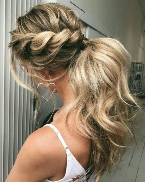 a low ponytail with two twisted braids on the sides and locks down