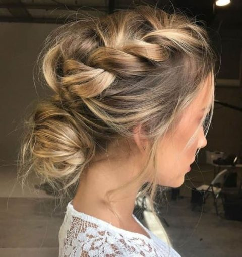 a messy braided updo with a low bun and a volume on top