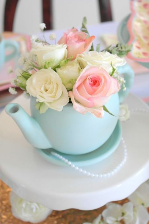 a mint-colored tea pot with pink and neutrla blooms and some pearls for a centerpiece