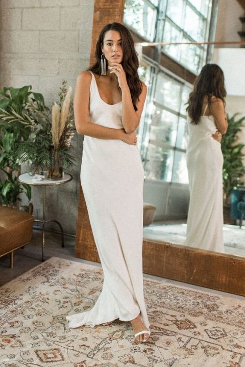 a modern relaxed plain slip wedding dress with a deep V-neckline plus statement earrings