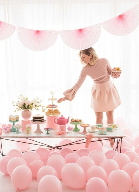 a pink bridal shower tea party with balloons, paper fans and a large dessert table