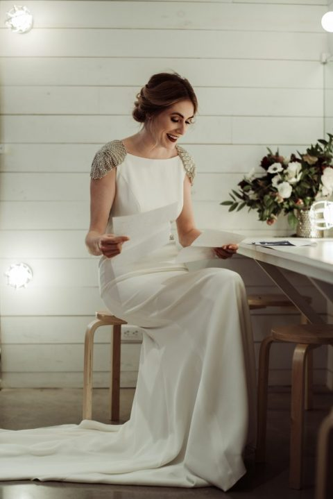 a plain sheath wedding dress with embellished cap sleeves, a train and an open back