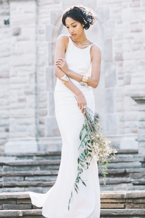 a plain sheath wedding gown with a high neckline, spaghetti straps and a small strain