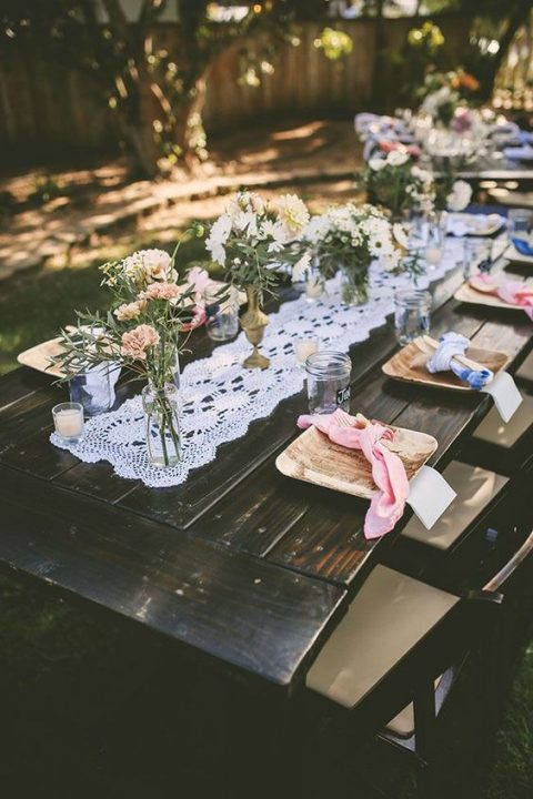 a relaxed tablescape with a macrame runner, neutral bloom centerpieces and wooden chargers