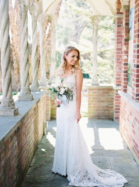 a romantic lace sleeveless wedding dress with wide straps and a V-neckline plus a train