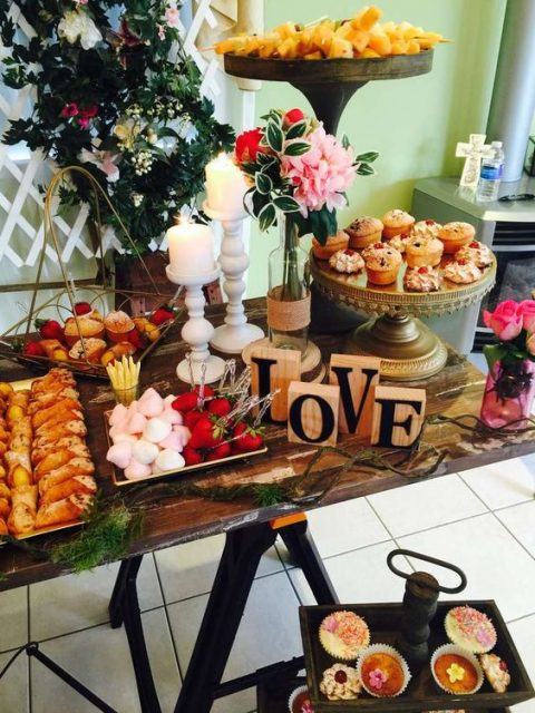 a rustic dessert table for a tea party bridal shower - lots of cupcakes, sweets, marshmallows and fruits