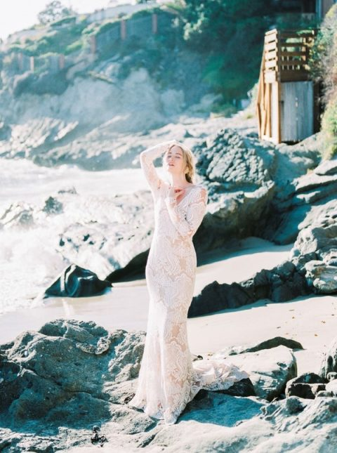 a sheer lace sheath wedding gown with a deep V-neckline, long sleeves and a train