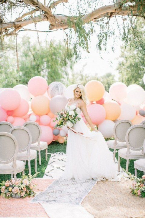 a soothing pastel balloon wedding backdrop in pink, peachy, soft orange and grey