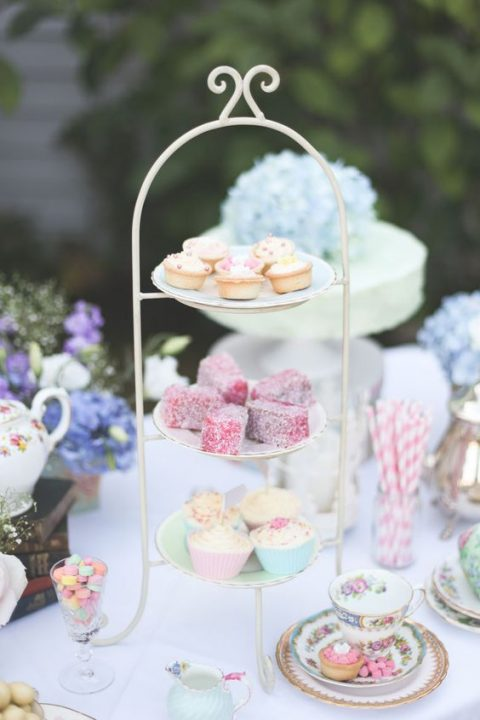 a stand with pastel desserts, candies in glasses and vintage teaware