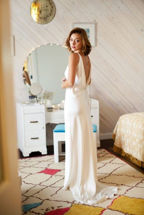 a stylish slip wedding dress with layered back necklaces to highlight its cutout