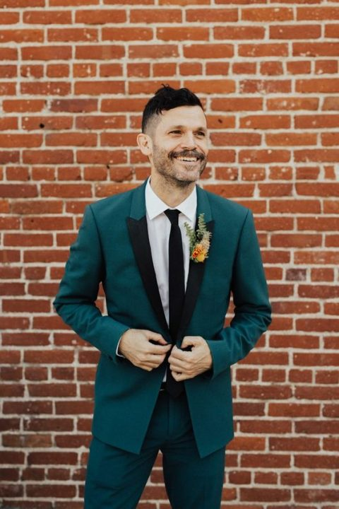a teal groom_s suit with black lapels and a black tie