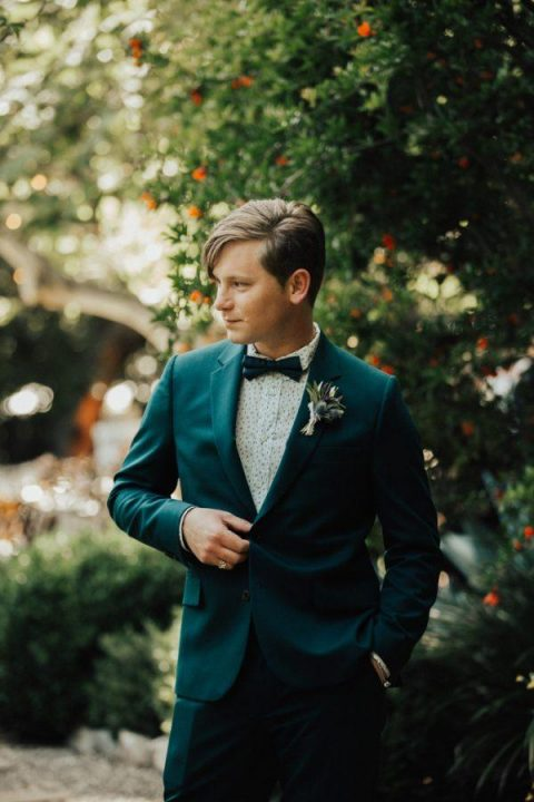 a turquoise suit, a printed shirt and a teal bow tie plus a thistle boutonniere