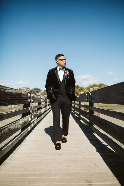 a velour jacket tux, a blue bow tie, a bold boutonniere and black embroidered velvet loafers for a dashing touch
