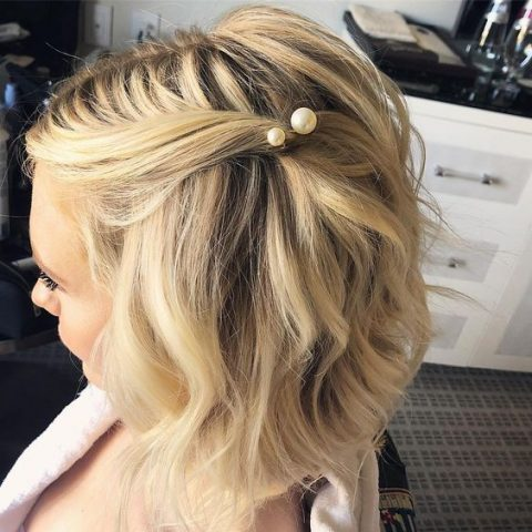 a wavy medium length haircut with some hair tucked with a pearl hairpin