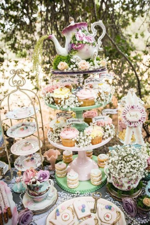 a whimsy vintage sweets table with vintage cups, saucers and a tea pot plus baby_s breath centerpieces
