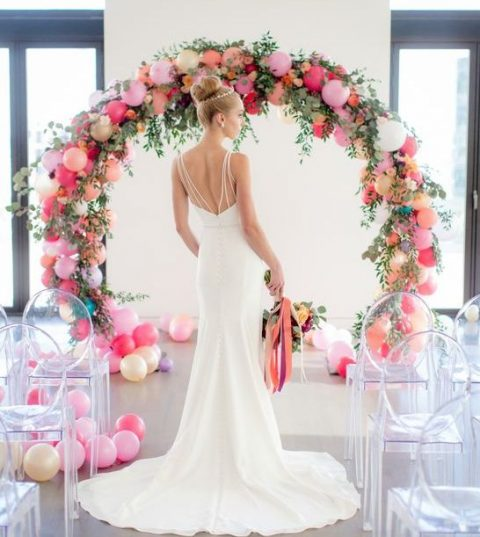 a whimsy wedding arch of colorful balloons, greenery and flowers