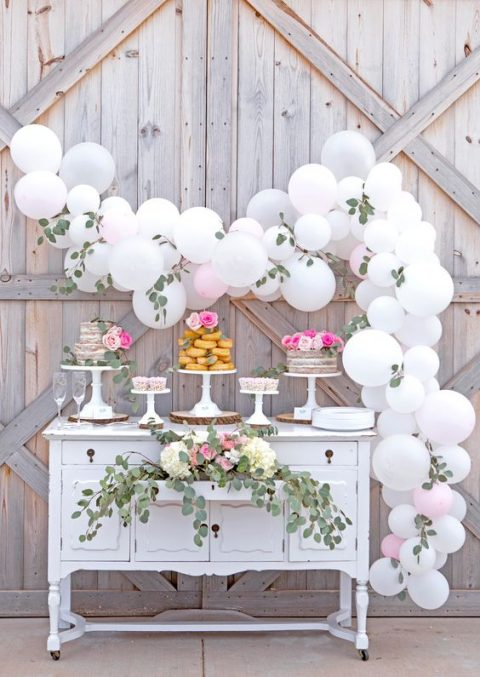 a white balloon and foliage garland over the dessert table